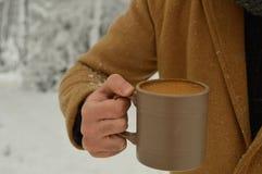 Taza masculina de la tenencia de la mano de caf? con el fondo nevoso foto de archivo