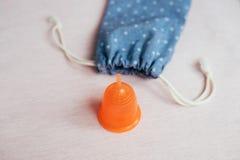 Taza menstrual anaranjada cerca del bolso del algodón en fondo rosado imagenes de archivo