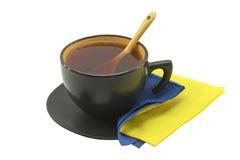 Taza negra con té negro Fotos de archivo