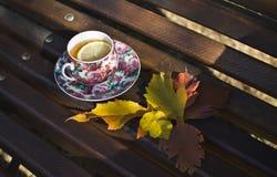 Taza negra rosada de té con el limón en banco de madera marrón en parque del otoño Fotografía de archivo