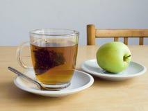 Taza o té con la bolsita de té y la manzana Foto de archivo libre de regalías