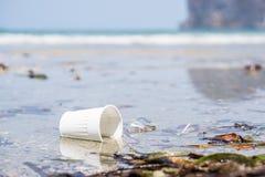 Taza plástica blanca en la playa Foto de archivo