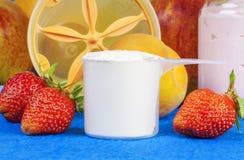 Taza plástica de polvo de la proteína con las fresas alrededor Imagenes de archivo