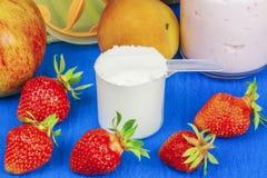 Taza plástica de polvo de la proteína con las frutas alrededor Imagen de archivo