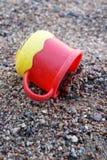 Taza plástica en la arena Fotografía de archivo libre de regalías