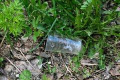 Taza plástica en la hierba Fotos de archivo