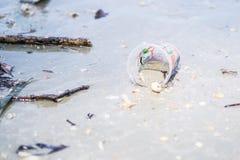 Taza plástica en la playa Foto de archivo libre de regalías