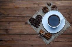Taza, postre y especias de café en una tabla de madera vieja, visión superior Foto de archivo libre de regalías