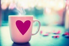 Taza preciosa con el corazón rosado en travesaño de la ventana en el fondo de la naturaleza de la tarde con el bokeh, vista delan Fotografía de archivo