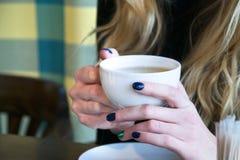 Taza que se sostiene femenina de té en un café Imagen de archivo libre de regalías