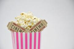 Taza rayada de palomitas con los boletos de la película foto de archivo