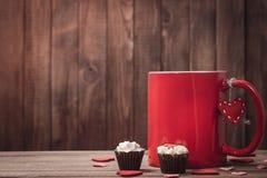 Taza roja con café y chocolates el día de tarjeta del día de San Valentín Imágenes de archivo libres de regalías