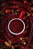 Taza roja con la pimienta roja de tierra rodeada por las vainas secas de la pimienta roja, visión superior, primer imagenes de archivo
