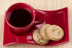 Taza roja con las galletas del café y de la harina de avena imágenes de archivo libres de regalías