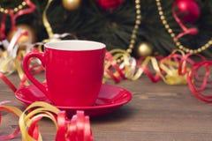 Taza roja de café, de juguetes de la Navidad y de flámulas Imagen de archivo