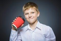 Taza roja de la bebida del muchacho de café aislada en fondo gris Imagen de archivo libre de regalías