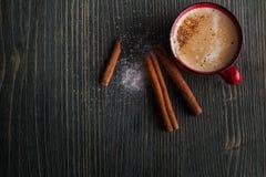 Taza roja de la cerámica de café con canela Foto de archivo