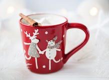 Taza roja de la Navidad con cacao y canela y marshmellows Fotografía de archivo libre de regalías