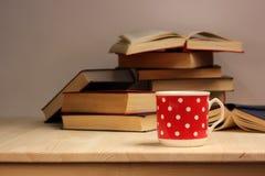 Taza roja de la porcelana con los lunares blancos y una pila de libros foto de archivo libre de regalías