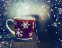 Taza roja de los copos de nieve del invierno con la bebida caliente del té en la tabla rústica con nieve imagenes de archivo