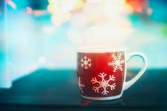 Taza roja de los copos de nieve del invierno en la tabla con el bokeh foto de archivo libre de regalías