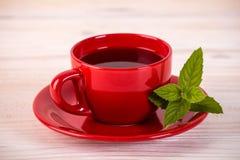 Taza roja de té con las hojas verdes Imagenes de archivo