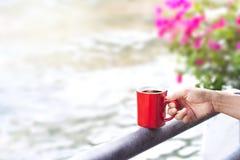Taza roja del café en una cerca del fondo de la naturaleza del canal Fotografía de archivo libre de regalías