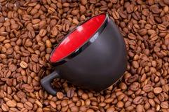 Taza roja en el fondo de los granos de café Fotos de archivo