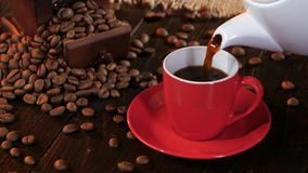 Taza roja en el platillo con café express caliente del café sólo estudio metrajes
