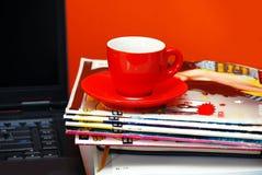 Taza roja en los compartimientos y el cuaderno sobre rojo Fotografía de archivo libre de regalías