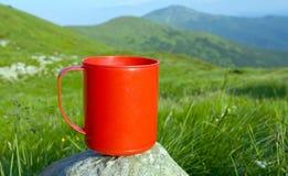 Taza roja en piedra en campo de las montañas imagen de archivo libre de regalías