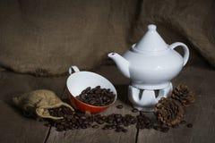 Taza roja, granos de las teteras y de café en de madera Foto de archivo libre de regalías
