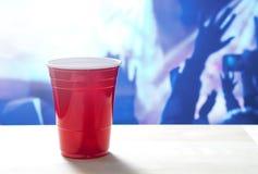 Taza roja plástica del partido en una tabla Club nocturno por completo de la gente que baila en la sala de baile en el fondo Imagenes de archivo
