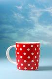Taza roja sobre fondo hermoso del cielo azul fotografía de archivo libre de regalías