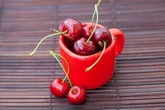 Taza roja y una cereza en una estera de bambú Imagen de archivo libre de regalías