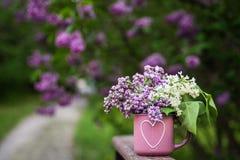 Taza rosada con el pequeño ramo de flores de la lila imagen de archivo