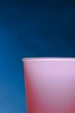 Taza rosada en un fondo azul Imágenes de archivo libres de regalías