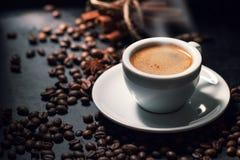 Taza sabrosa fresca del café express de café caliente con los granos de café en oscuridad Foto de archivo