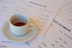 Taza semivacía de té en documentos financieros Imagen de archivo libre de regalías