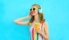 Taza sonriente feliz de la tenencia de la mujer del retrato de jugo que escucha la m?sica en auriculares inal?mbricos en azul col imagen de archivo