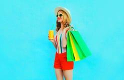 Taza sonriente feliz de la tenencia de la mujer de zumo de fruta con los bolsos de compras que llevan la camiseta colorida, sombr imágenes de archivo libres de regalías