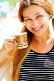 Taza sonriente hermosa de la mujer y de café Foto de archivo libre de regalías