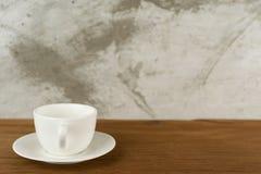 Taza, taza de café en la madera de la tabla detrás del hormigón de la falta de definición Imagen de archivo libre de regalías