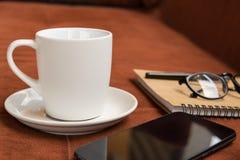 Taza, taza de café y smartphone con la nota del diario sobre la alfombra roja o Imagen de archivo