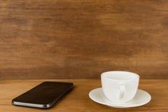 Taza, taza de café y teléfono elegante en el tablero de madera delante del Br Fotos de archivo