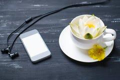 Taza, teléfono móvil, auriculares y lirio de agua en un fondo de madera Foto de archivo libre de regalías