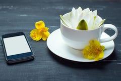 Taza, teléfono móvil y lirio de agua en un fondo de madera Fotos de archivo libres de regalías