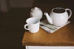 Taza, tetera en la tabla de cocina Foto de archivo