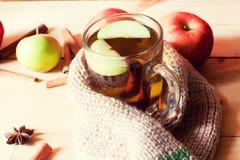 Taza transparente con una bebida y una manzana calientes envueltas en una bufanda que se calienta en una tabla de madera Fotos de archivo
