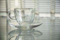 Taza transparente vacía en una tabla de cristal Foto de archivo